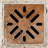 Rusty drain grate in concrete floor