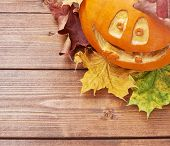foto of jack-o-lantern  - Jack o lantern smiling happy pumpkin composition over the maple leaves and wooden surface - JPG