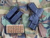 picture of ammo  - Top view angled shot of United States military uniform weapon clips and box of ammo in horizontal layout - JPG