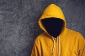 picture of jacket  - Faceless unknown and unrecognizable person without identity wearing yellow hooded jacket - JPG