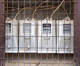 picture of electricity meter  - Group of old dirty electricity meters behind a metal grill - JPG