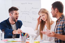 picture of shout  - Two frustrated business people sitting at the table and gesturing while their furious boss holding paper and shouting - JPG