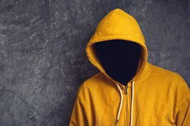 pic of incognito  - Faceless unknown and unrecognizable person without identity wearing yellow hooded jacket - JPG