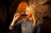 picture of wine cellar  - Beautiful young woman tasting red wine in a wine cellar - JPG