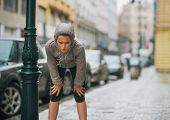 picture of breath taking  - A woman jogger leans down to breathe deeply taking a break and stretching. She is wearing rain gear for her workout. ** Note: Visible grain at 100%, best at smaller sizes - JPG