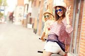 foto of tandem bicycle  - A picture of two girl friends riding a tandem bicycle in the city - JPG