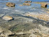 foto of tide  - wild seascape with low tide and surfacing rocks - JPG