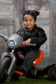 pic of tricycle  - Adorable mixed race toddler wearing a bandanna and leather jacket and riding a toy tricycle - JPG