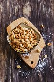 foto of salt-bowl  - salted peanut nuts in a bowl on the old wooden background - JPG