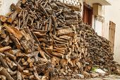 stock photo of firewood  - Firewood stacked in front of a village house - JPG