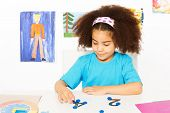 foto of numbers counting  - African girl puts blue coins on numbers learning to count during developmental game at the desk while sitting in playroom with wall with kids drawings - JPG