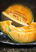 pic of cantaloupe  - Cantaloupe Melon on vintage metal plate on wooden table - JPG