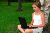 image of school child  - young girl sitting in a park with laptop computer - JPG