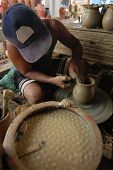 picture of loam  - Young potter creating a clay pot on a Potters wheel - JPG