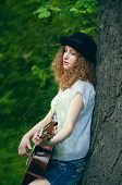 picture of nostalgic  - Young girl wearing black hat with guitar leaning on a tree feeling nostalgic - JPG