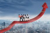 picture of rope pulling  - Group of business people standing on arrow and pulling it upward by using a rope - JPG