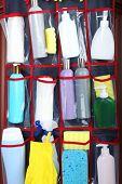 image of detergent  - Different detergents in hanging bag wooden door - JPG
