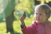 stock photo of edible  - Curious two years old preschooler girl with short pigtails is holding edible snail with brown striped shell