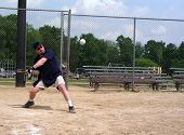 Man At A Baseball Diamond About To Hit A Softball (Baseball) With Ball Frozen In Air