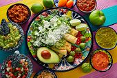 Green enchiladas Mexican food with guacamole and sauces on colorful table poster