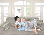 Mother and baby laugh together at home. They are sitting on the sofe in a brightly lit living room.
