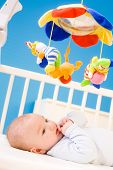Four months old baby resting on crig at nursery and plying with his little thumb. Toys are officiall