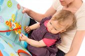 Mother reading for baby girl (9 months) from story book.