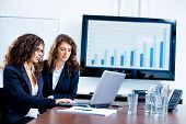 Young businesswomen sitting by meeting table at office in front of a huge blank plasma TV screen and