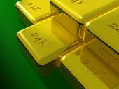 24K gold bars arranged on a green table