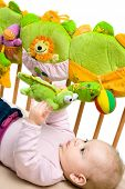 Baby lying on back on bed palying, white background.