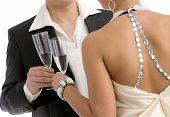 Manos sosteniendo flautas de champán, el tintinear. Aislados sobre fondo blanco.