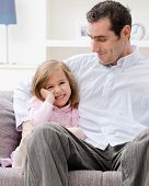 Little girl wearing pink dress sitting on couch embraced by her father, smiling.