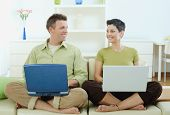 Happy young couple sitting on couch at home using laptop computer, smiling.