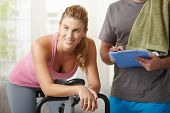Young woman training on exercise bike with personal trainer at home, smiling.