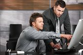 stock photo of computer-screen  - Two businessmen working together with computer at office desk - JPG