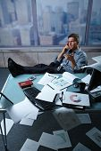 Tired businessman calling from office with shoes off fees up on table papers lying all around, pictu