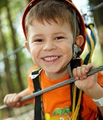 Portrait of happy little boy having fun in adventure park smiling to camera wearing mountain helmet