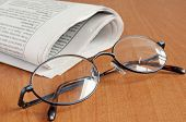 Dark-rimmed glasses and a newspaper