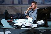 Tired businessman taking break speaking on landline phone with shoes off feet up on office desk holding glasses.