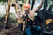 Sexy Builder Concept. Muscular Builder In Hard Hat Shows Biceps, Poses. Sexy Man With Nude Torso Nea poster