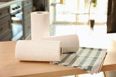 Rolls of paper towels and dishcloth on table indoors poster