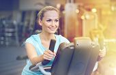 sport, fitness, lifestyle, technology and people concept - smiling woman exercising on exercise bike poster