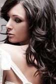 beautiful female with long wavy hair black hair, studio portrait