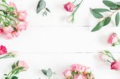 Flowers Composition. Frame Made Of Eucalyptus Branches And Pink Rose Flowers On White Wooden Backgro poster