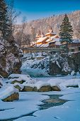 Wooden Church Above The Winter River In A Carpathian Mountains. poster