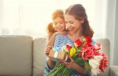 Happy Mothers Day! Child Daughter   Gives Mother A Bouquet Of Flowers To Tulips And Gift. poster