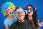 Young people in funny disguise posing on color background. April fools day celebration poster