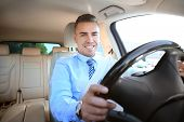 Man in formal wear on drivers seat of car poster