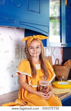 poster of Little Girl In A Yellow Dress Holds A Jar Of Raw Pasta On The Background Of The Kitchen At Home. Lit