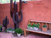 foto of hacienda  - A Southwestern style stucco patio with cactus sculptures bench and flowers - JPG